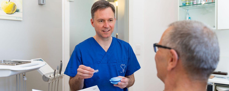 Der Zahnarzt zeigt einem Patienten Aligner-Schienen in der Zahnarztpraxis Dr. Christian Schubert in Beeskow